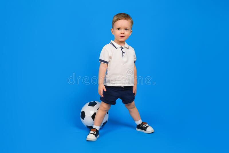 Small happy boy in football uniform and a soccer ball stands on a blue background. football champion. stock photography
