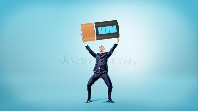 A small happy businessman smiles and holds a huge fully charged battery over his head. stock images