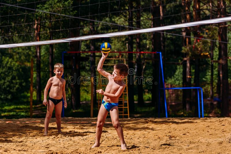 Small happy children playing beach volleyball royalty free stock photos