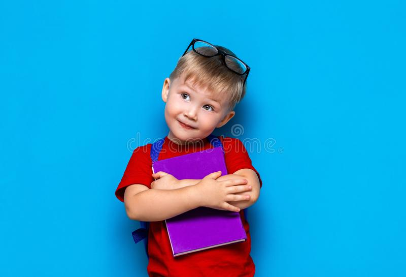 Small happy smiling boy with glasses on his head, book in hands, schoolbag on his shoulders. back to school. ready to school.  royalty free stock photo