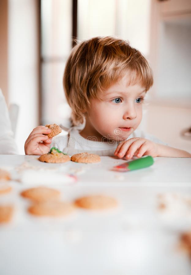 A small toddler boy sitting at the table, decorating and eating cakes at home. A small happy toddler boy sitting at the table, decorating and eating cakes at stock image