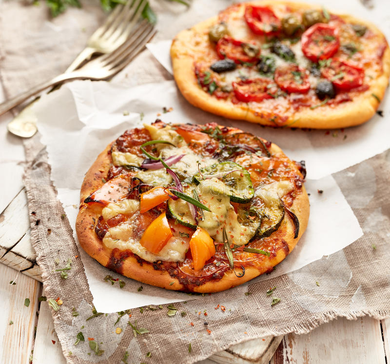 Small homemade vegetable pizzas on a white wooden table. Vegetarian pizzas with addition of zucchini, bell pepper, cherry tomatoes, olives and herbs stock images