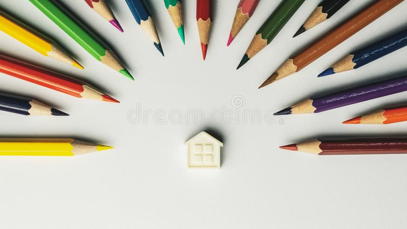 Small house and crayons on white background - vintage style royalty free stock photography