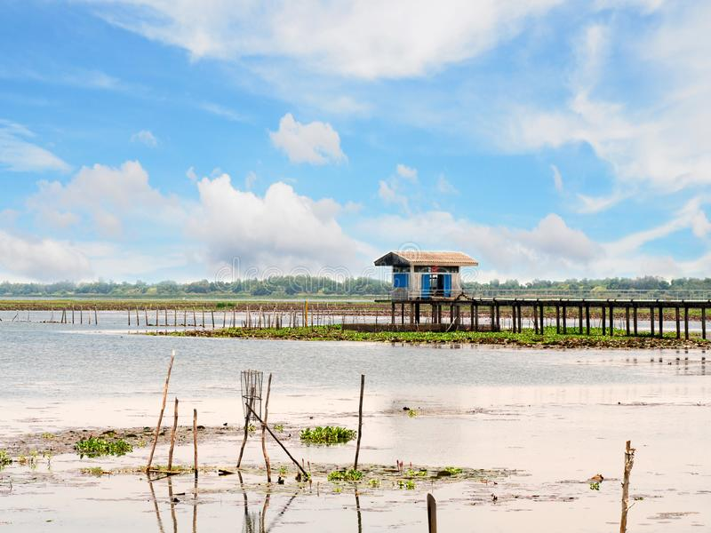 Small house in lake river for keep tool equipment of fisherman in sunny day with blue sky and white cloud stock photo