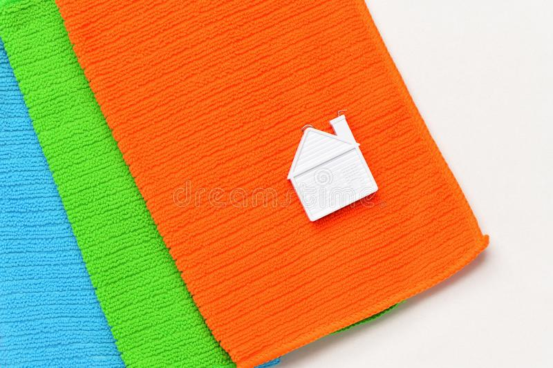 A small house lies on a stack of three towels on a white background. Top view close-up royalty free stock images