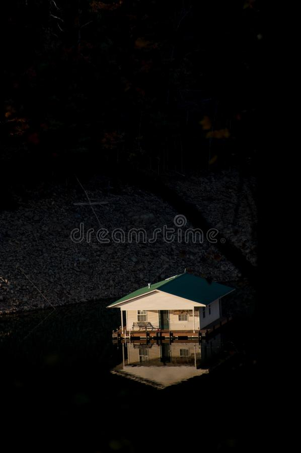 A small boat house lit by bright sunlight floats in a reservoir lake. A small house lit by bright sunlight floats in a reservoir lake in North Carolina, USA stock image