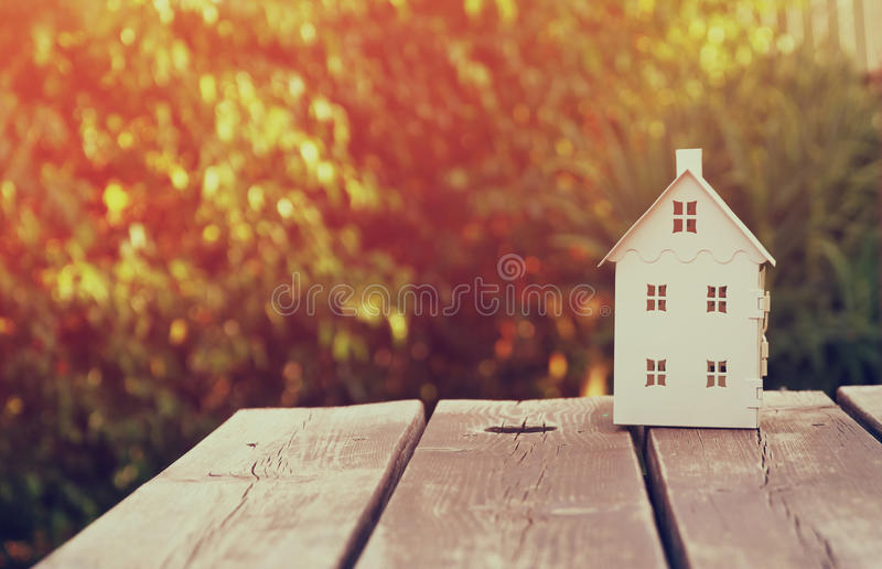 Small house model over wooden table outdoors at garden . filtered image. selective focus royalty free stock images
