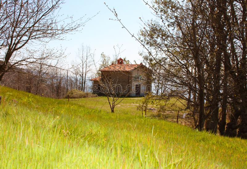 Small house in the mountains abandoned in a large green clearing on the Apuan Alps in Tuscany, Tuscan Apennines.  royalty free stock photography