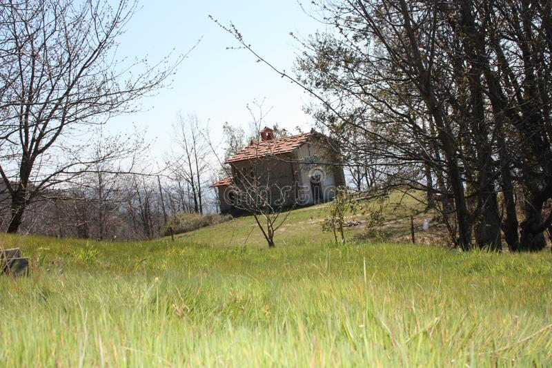 Small house in the mountains abandoned in a large green clearing on the Apuan Alps in Tuscany, Tuscan Apennines.  stock photo