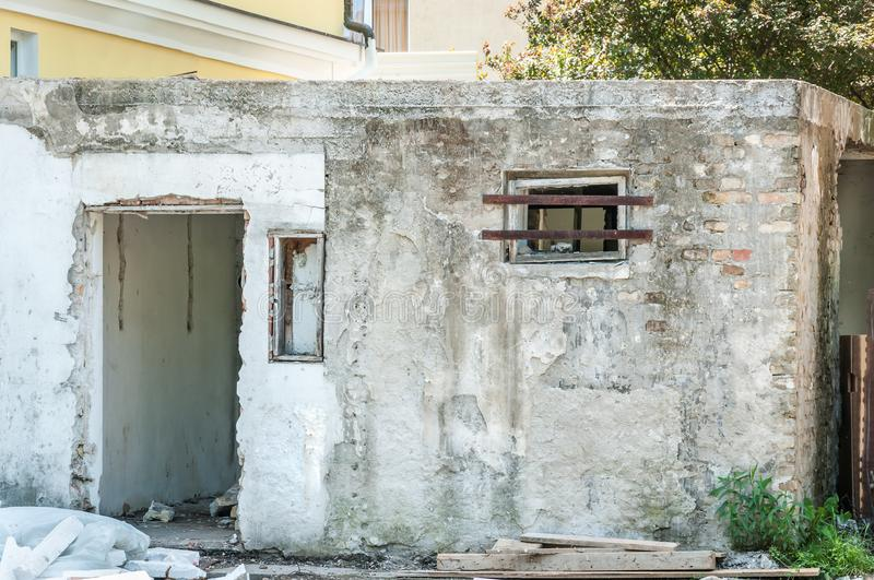 Small house near building with damaged door and walls with bullet holes used as improvised hidden prison with bars on the window i royalty free stock photography