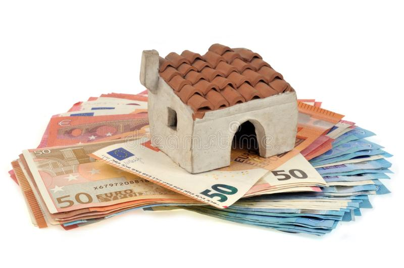 Small house posed on banknotes. House and banknotes in euro on white background royalty free stock image