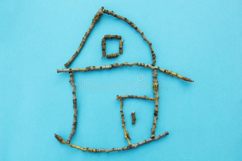 Small house of sticks on a blue background, concept.  royalty free stock image