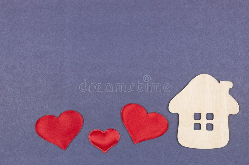 A small house and three red hearts on a gray-blue background. The concept of love, happiness in your home. A home for a family with children. Real estate royalty free stock photos