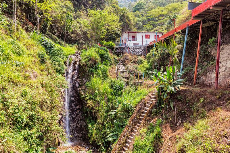 Landscape at the countryside near Medellin, Colombia. Small house, tropical rain forest and small waterfall at the countryside near Medellin, Colombia royalty free stock photo