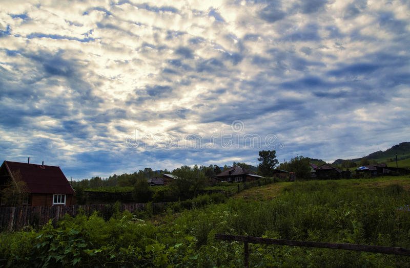 Small house in the village, dark clouds on a blue sky and green grass in the valley of a mountain.  royalty free stock images