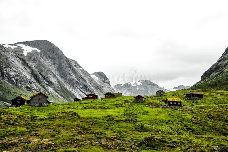 Mountain village with small houses and wooden cabins with grass on the roof in a valley. The huts are standing on green grass and stock photos