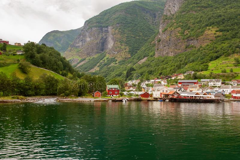 Small houses of the commune on the fjord, photographed from a sightseeing cruise ferry departing in summer from Flam, Norway. View of a village on edge of the stock images