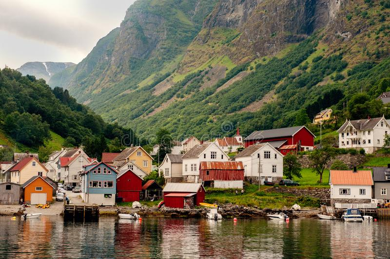 Small houses of the commune on the fjord, photographed from a sightseeing cruise ferry departing in summer from Flam, Norway. View of a village on edge of the stock photos