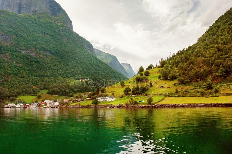 Small houses of the commune on the fjord, photographed from a sightseeing cruise ferry departing in summer from Flam, Norway. View of a village on edge of the stock photography