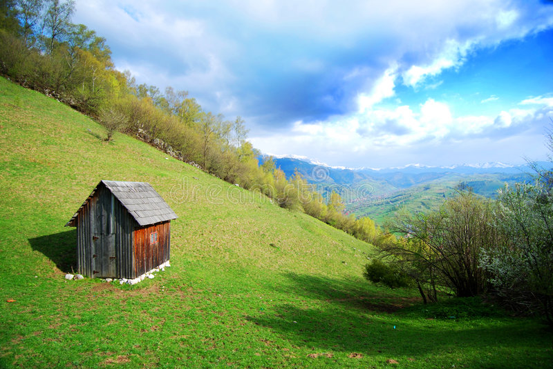 Small Hut on a Hillside. A small wooden hut on the hillside in Romania royalty free stock photography