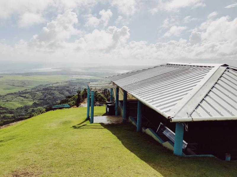 The small hut on the Redonda Mountain. Beautiful view at the small hut on the Redonda Mountain and green hills of Dominican Republic. Sky has huge clouds, but royalty free stock images