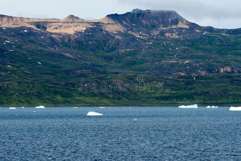 Icebergs in front of Seashore with Mountains, Greenland. Huge Iceberg building with tower. Small icebergs on seaside near Ilulissat, Disko Bay, Greenland stock images