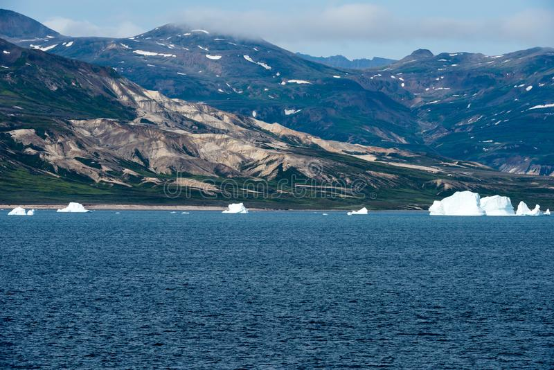 Icebergs in front of Seashore with Mountains, Greenland. Huge Iceberg building with tower. Small icebergs on seaside near Ilulissat, Disko Bay, Greenland royalty free stock photo