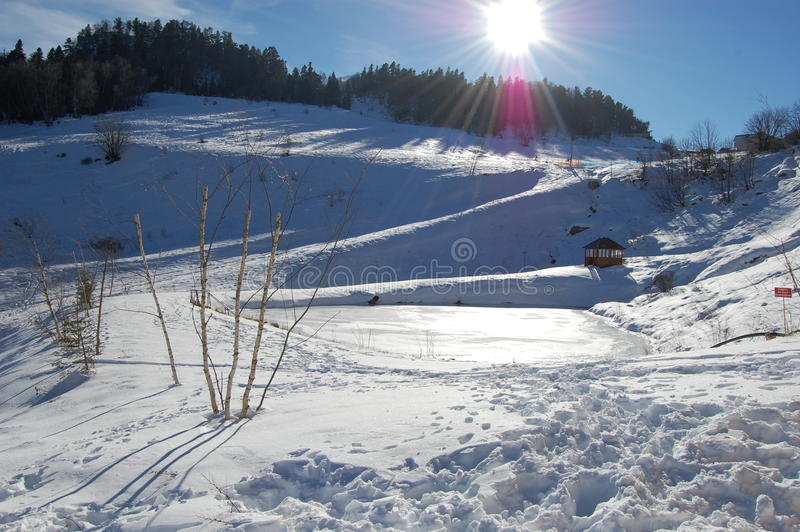 A small icy mountain lake after a frozen winter stock photo