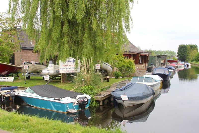 Small idyllic Dutch village Kortenhoef with boats in a canal, Netherlands. Small idyllic village Kortenhoef along a canal, province North Holland, Netherlands royalty free stock image