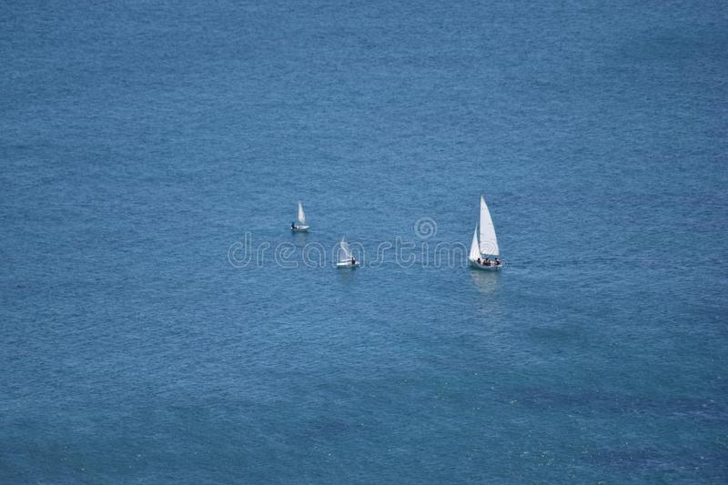 Sailboats in the mediterranean sea, Alicante Spain. Perspective photo of a group of sailboats sailing through the Mediterranean, Alicante Spain royalty free stock image