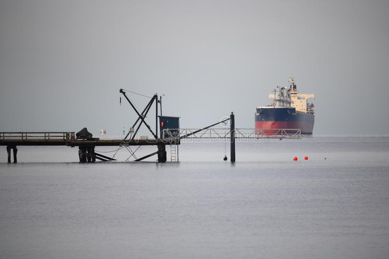 Small Industrial Pier. A pier used for light off-loading work, stretches into the ocean where a freighter waits to unload royalty free stock photo