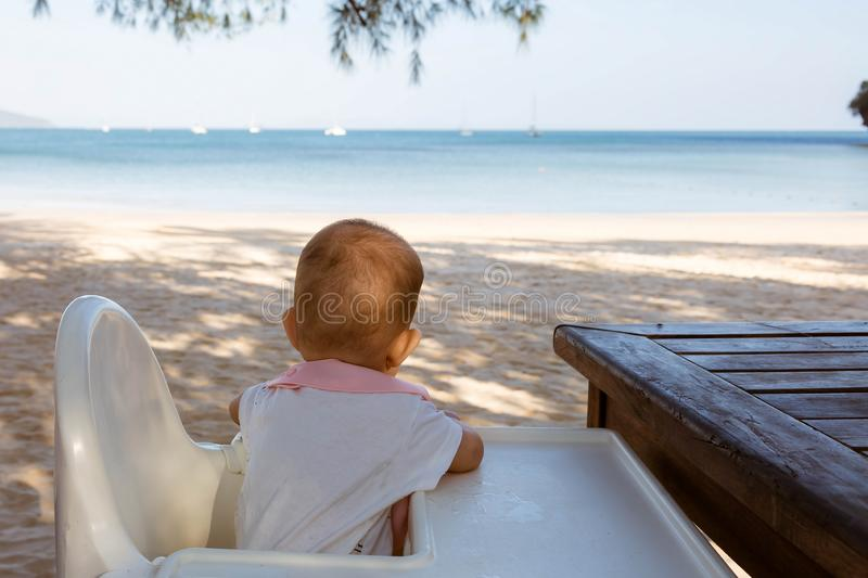 A small infant baby sits in a children chair at a special table and looks at the sandy beach and the sea.  royalty free stock photography