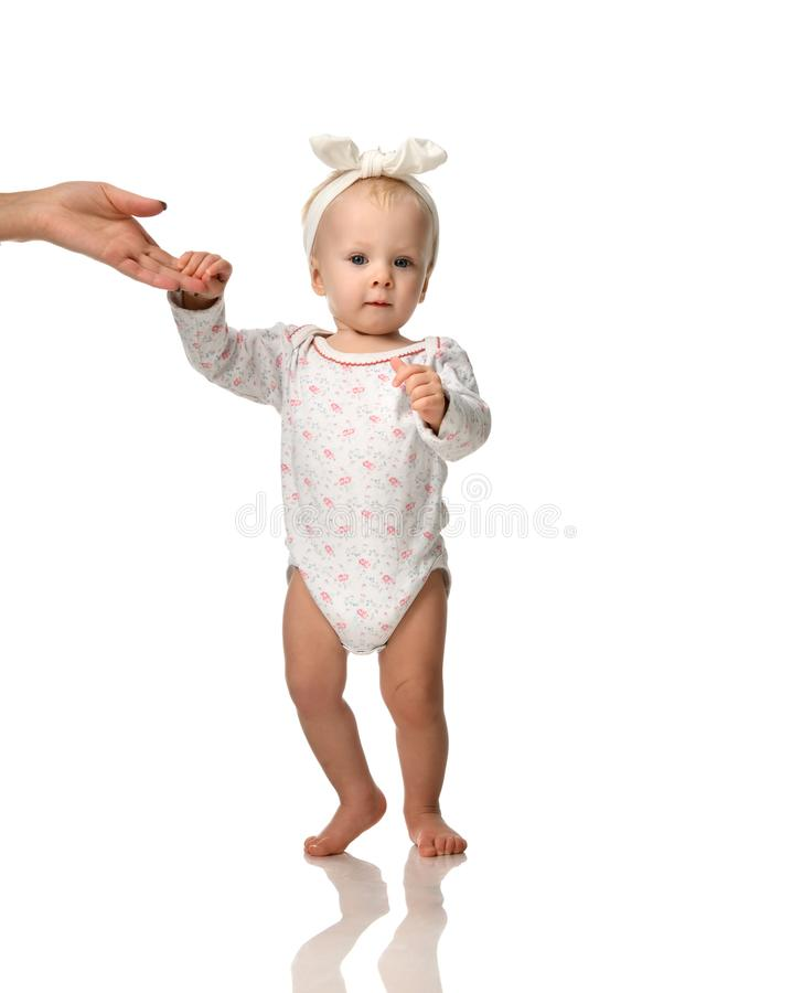 Small infant child baby girl toddler make first steps with mother hand help stock photo