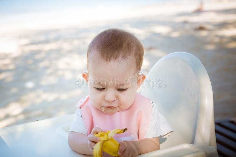A small infant child, a girl, enthusiastically picks a banana. Baby Eeats fruit on the beach sitting on a white children`s chair.  stock photography