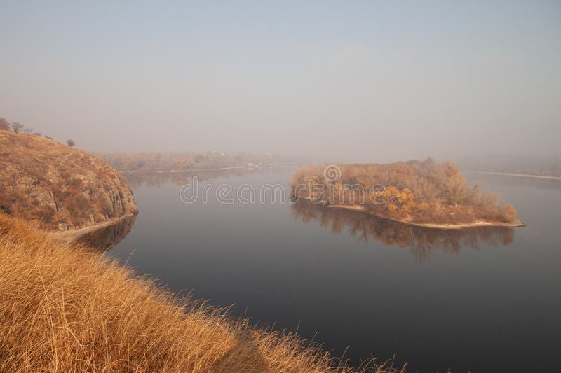 A small island as if floating in the middle of a river, shrouded in morning fog royalty free stock image
