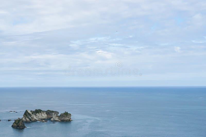 Small island on blue Tasman sea in New Zealand. With blue sky stock photos
