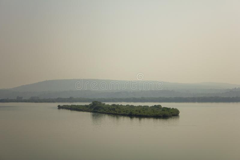 Small island with bright green trees against the backdrop of a misty river valley stock photos