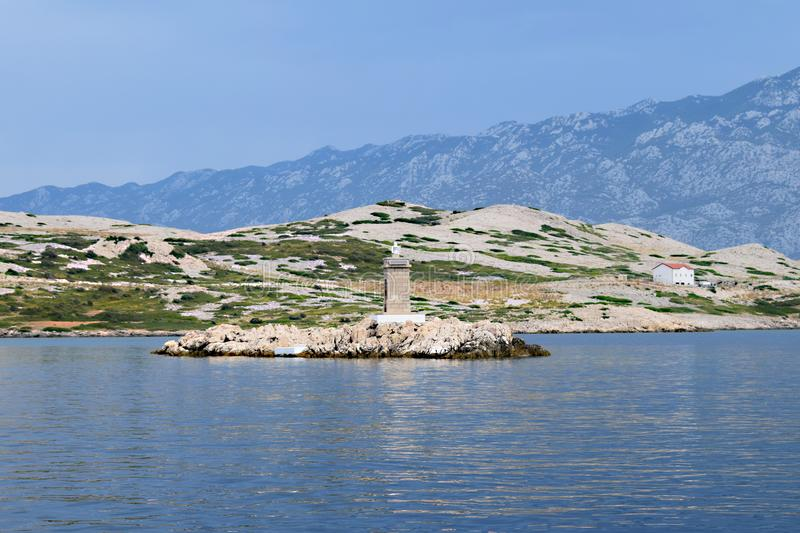 Small island with lighthouse. Behind is island of Rab and behind is mountain Velebit in Croatia stock images