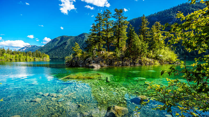 Small island in the middle of the crystal clear waters of Pavilion Lake in Marble Canyon Provincial Park, British Columbia. The lake has international fame stock photo