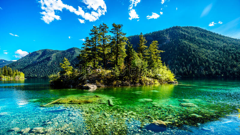 Small island in the middle of the crystal clear waters of Pavilion Lake in Marble Canyon Provincial Park, British Columbia. The lake has international fame stock photos