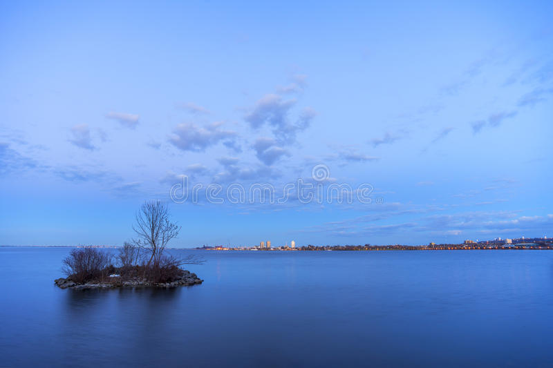 Small island in smooth lake at dusk hiding a nesting swan, safely removed from vibrant cityscape in the distance across the water royalty free stock image