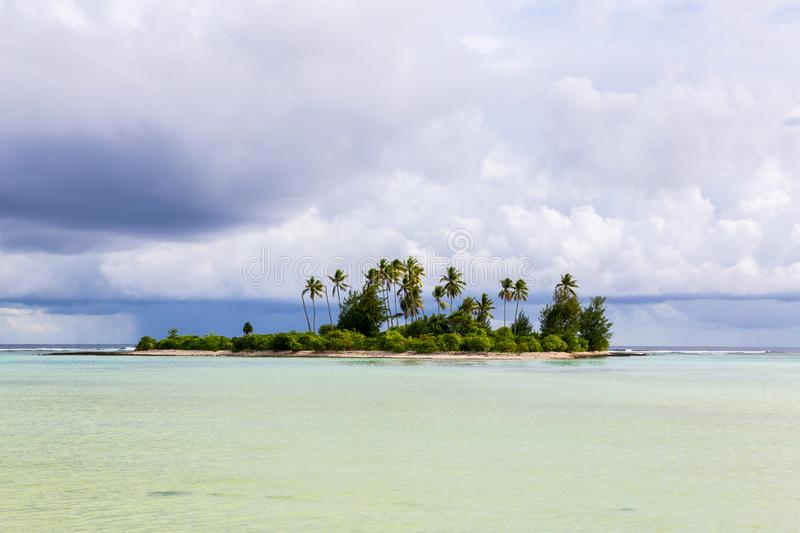 A small islet motu overgrown with palm forest somewhere in the lagoon of Tarawa atoll in bad cloudy weather, Kiribati, Oceania. royalty free stock image