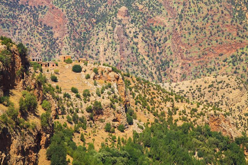 Small  berber village with clay houses on hill top against impressive red mountain face dotted with green plants. Ourika valley - Morocco stock photos