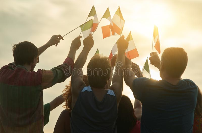 Small italian flags against sunshine background. Bright evening sky at the down stock image