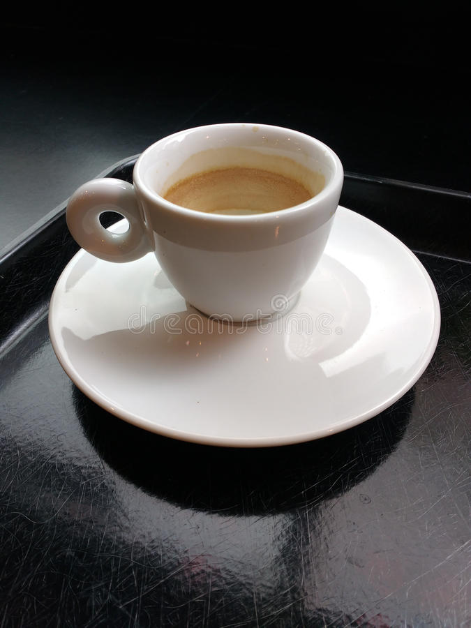 Small Ivory White Demitasse Espresso Cup with Matching Saucer on a Black Serving Tray, Coffee Foam Inside of the Cup stock photography