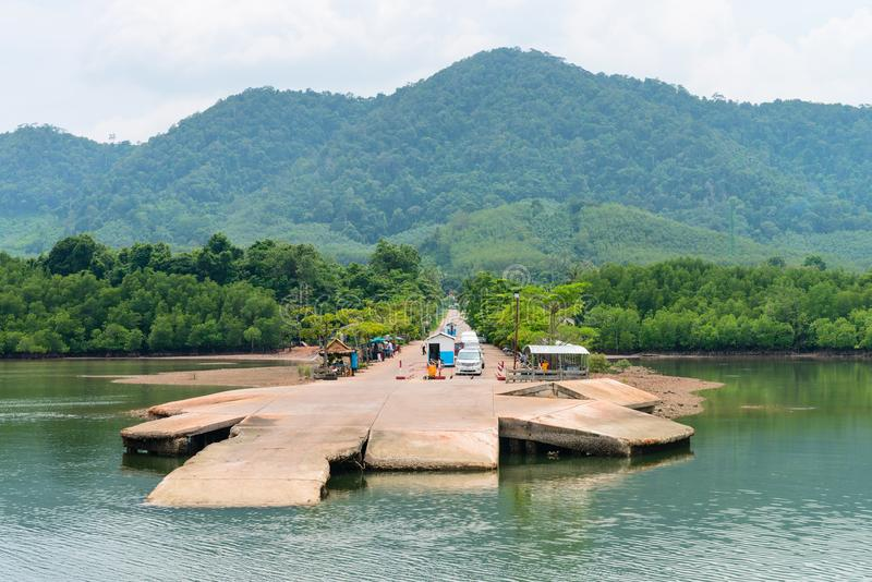 Small jetty for ferry on green tropical island. With cars in the line waiting for boarding on an vessel royalty free stock images