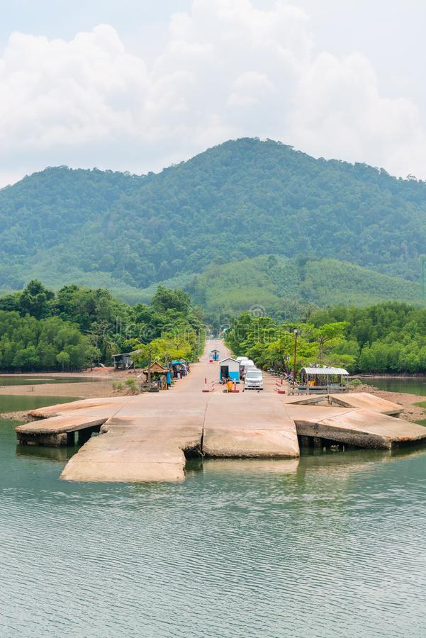 Small jetty for ferry on green tropical island. With cars in the line waiting for boarding on an vessel royalty free stock photography