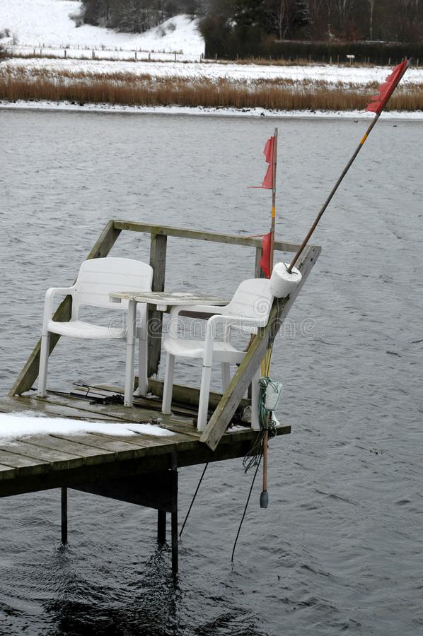 Small jetty with two chairs. stock photos