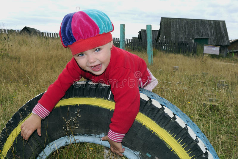 Download Small Joyful Girl On A Wheel In Village Stock Photo - Image: 23817954