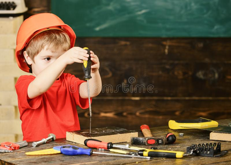 Small kid holding a screwdriver with both hands. Little boy discovered a new toy. Early learning concept stock images